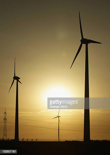 Wind turbines spin at sunset on August 20 2010 in Roedgen near Bitterfeld Germany Germany is investing heavily in renewable energy production...