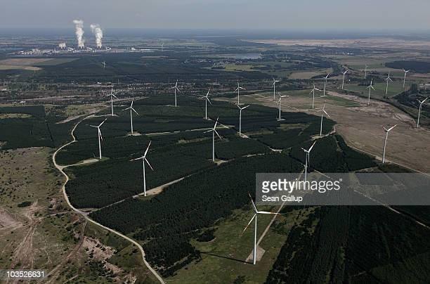 Wind turbines spin to produce electricity as steam rises from cooling towers at the Jaenschwalde coalfired power plant on August 20 2010 near...