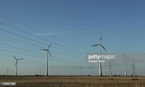 Wind turbines spin to produce electricity near high voltage power lines on August 20 2010 in Siebenhausen near Bitterfeld Germany Germany is...