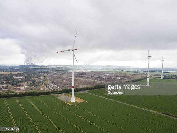 Wind turbines stand on the Innogy SE wind farm as the Garzweiler open cast lignite mine operated by RWE AG sits beyond in Bedburg Germany on Tuesday...