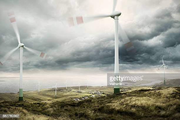 wind turbines with moving rotors and cloudy sky - spinning stock pictures, royalty-free photos & images