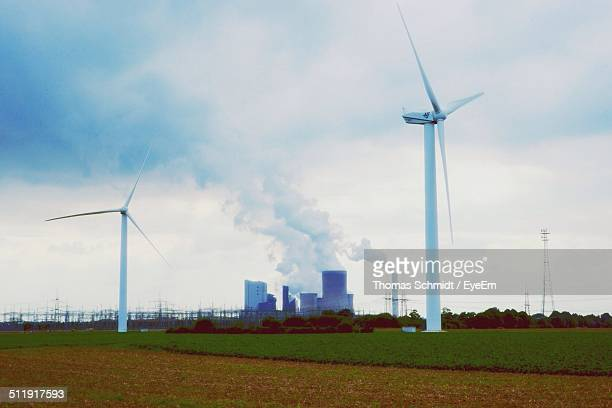 Wind turbines with nuclear power station in background