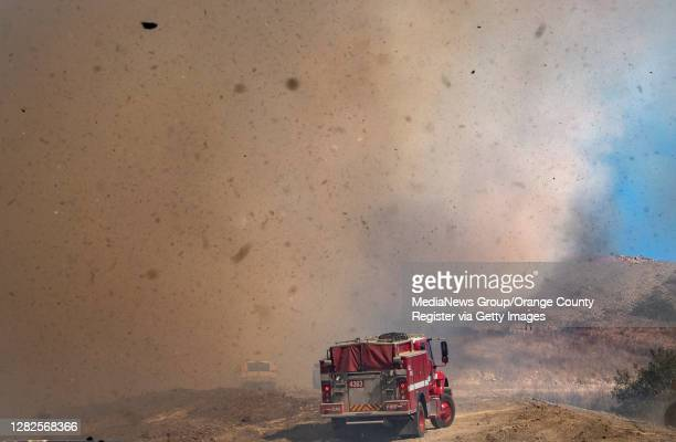 Wind whips up embers and ash as fire fighters battle flames on a fire road above homes in Foothill Ranch where a mandatory evacuation is in place on...