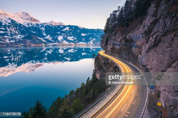 winding coastal road, switzerland - reflection pool stock pictures, royalty-free photos & images