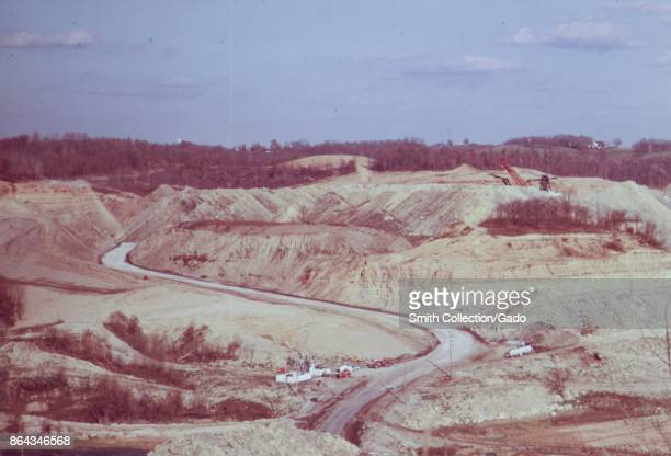Winding country road crossing a hilly barren landscape devastated by the coal strip mining Barnesville Ohio USA October 1973 Image courtesy National...