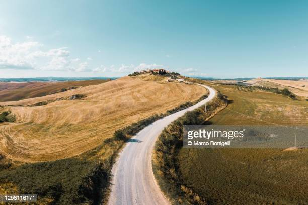 winding country road leading to a hilltop village, tuscany, italy - collina foto e immagini stock