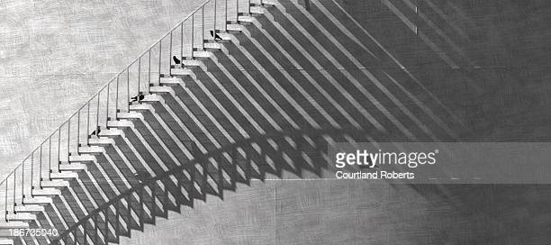 Winding exterior staircase on a huge oil storage tank with a flock of crows and shadow pattern in Vero Beach, Florida on July 26, 2013.
