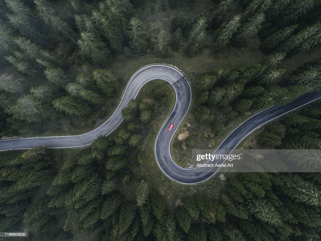 Winding forest road seen and a car shot by drone, Dolomites, Italy : Foto de stock