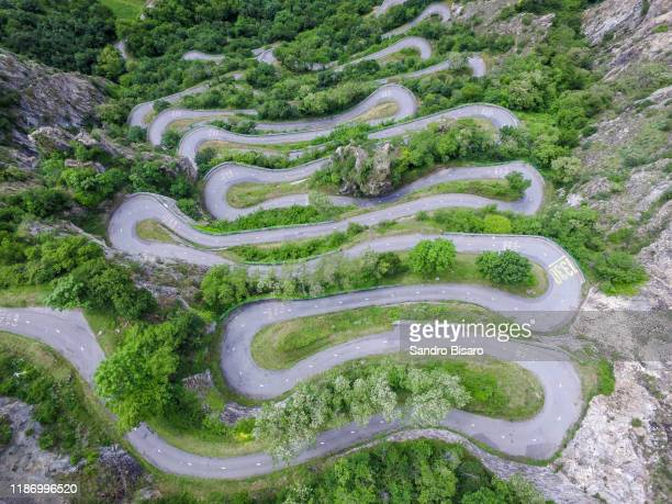 winding mountain road curves aerial view - auvergne rhône alpes stock pictures, royalty-free photos & images