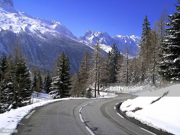 A winding mountain road with snowy mountains and evergreens