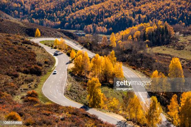 winding mountain roads in autumn - kashgar stock photos and pictures