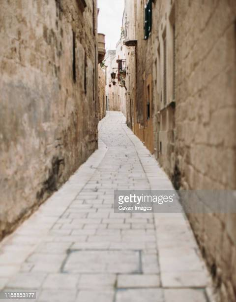 a winding narrow street in the mdina on the island of malta - midsection stock pictures, royalty-free photos & images