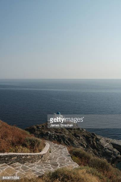 winding path leading to church of seven martyrs on rocky peninsula against the blue sea by kastro village, sifnos, cyclades islands, greece - peninsula de grecia fotografías e imágenes de stock