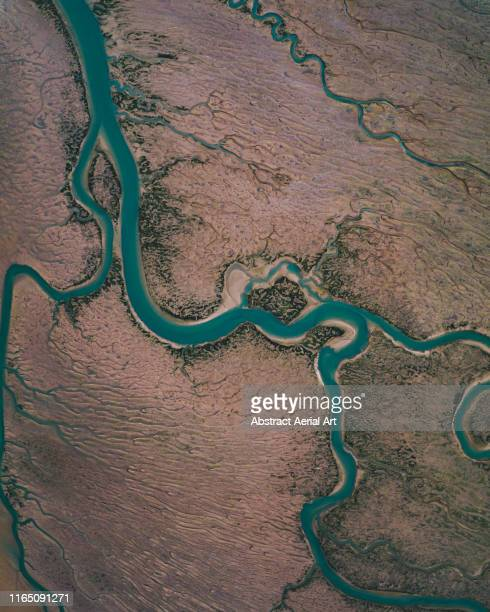 winding river channel at low tide as seen from drones point of view, lincolnshire, united kingdom - drone point of view stock pictures, royalty-free photos & images
