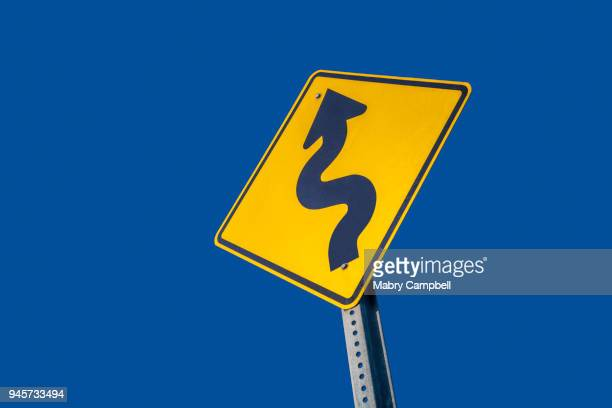 winding road ahead warning sign - road sign stock pictures, royalty-free photos & images