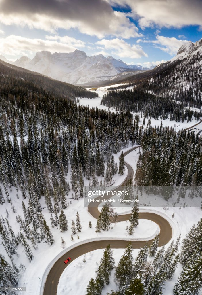 Winding road along snowy woods, aerial view, Antorno-Misurina, Dolomites, Italy : ストックフォト