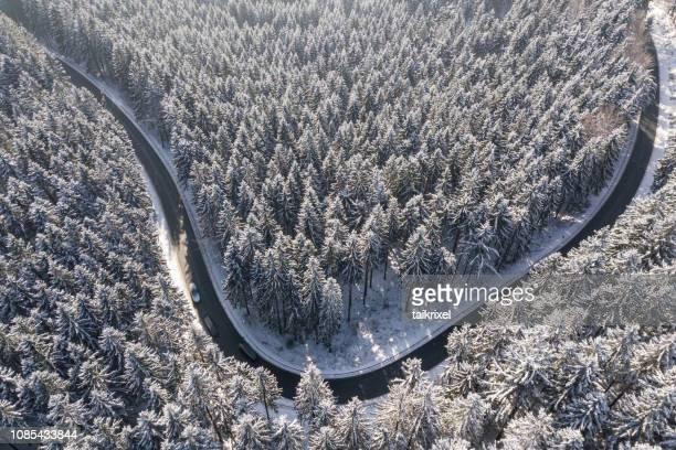 kurvenreiche straße im winterwald von oben, thüringen, deutschland, europa - finanzwirtschaft und industrie stock-fotos und bilder