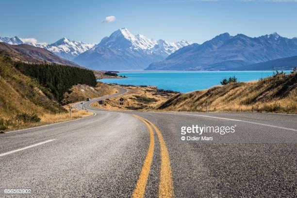 winding road leading to mt cook along lake pukaki in new zealand - neuseeland stock-fotos und bilder