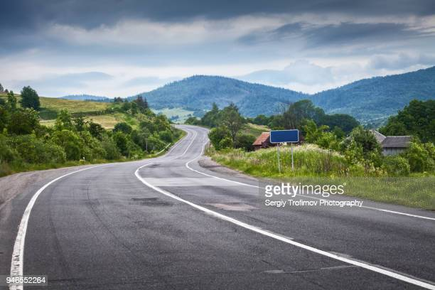 winding road over carpathian hills - two lane highway stock pictures, royalty-free photos & images