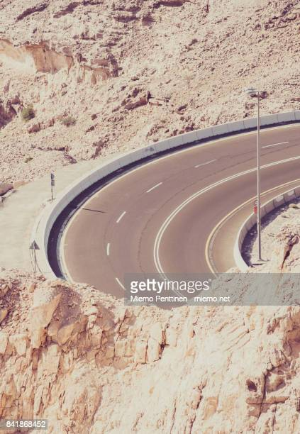 winding road rising to jebel hafeet mountain in al ain, uae - ジェベルハフィート ストックフォトと画像