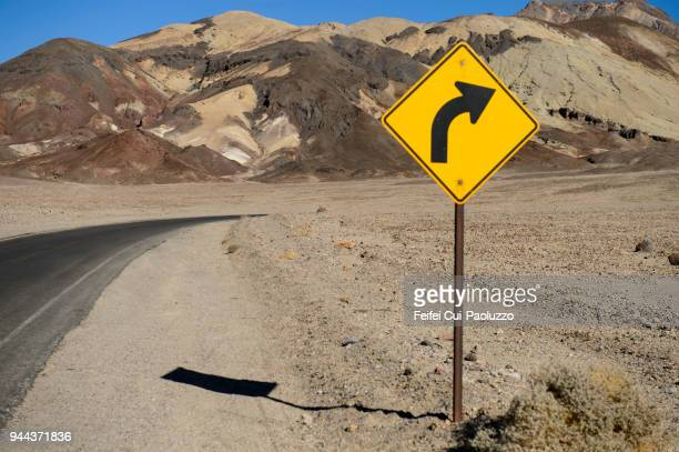 winding road sign and artist drive formation at artists dr, furnace creek, california, usa - road sign stock pictures, royalty-free photos & images