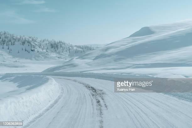 winding road through thick snow - 吹雪 ストックフォトと画像