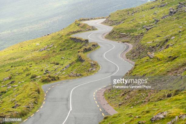 winding road to conor pass, ireland. - moving up stock pictures, royalty-free photos & images