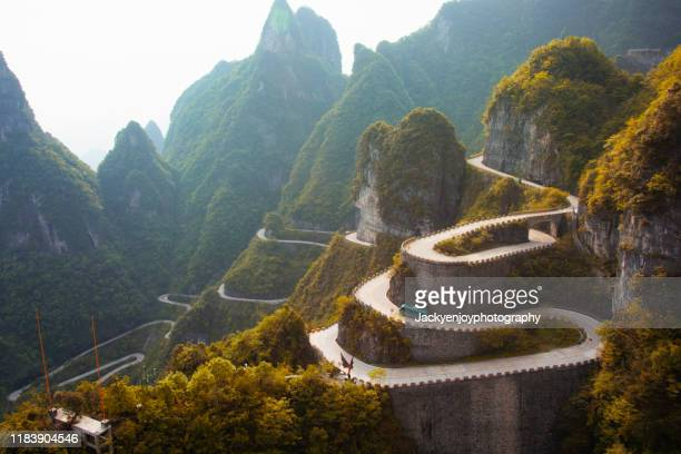 winding road with autumn forest, tianmxen mountain, zhangjiajie, hunan, china - extreme terrain stock pictures, royalty-free photos & images