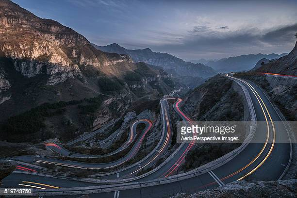 Winding road with hairpin bends at dusk with traffic lights