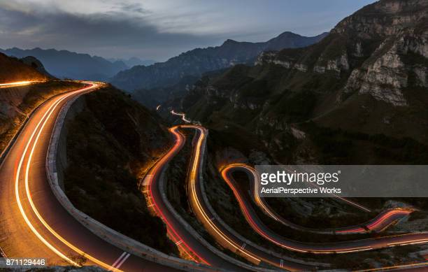winding road with hairpin bends up the at dusk with traffic lights - winding road stock pictures, royalty-free photos & images