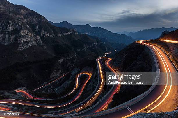 Winding road with hairpin bends up the rocky mountain at dusk with traffic lights