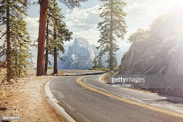 winding road with half dome in yosemite - nature stock pictures, royalty-free photos & images