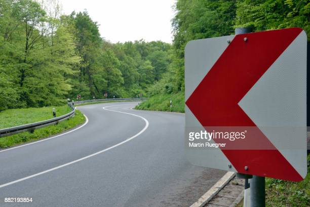 winding road with road sign through forest. - curved arrows - fotografias e filmes do acervo