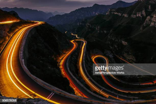 winding road with traffic lights - light trail stock pictures, royalty-free photos & images