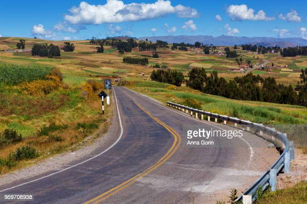Winding two-lane road through farmland between Cusco city and Moray, Peru, autumn afternoon