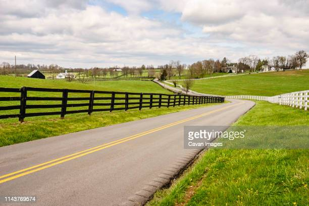 winding two-lane rural road in bluegrass region of kentucky - kentucky stock pictures, royalty-free photos & images