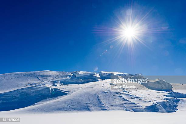 the antarctic sun rises over a crevasse field above the ross ice shelf. - ross ice shelf stock photos and pictures