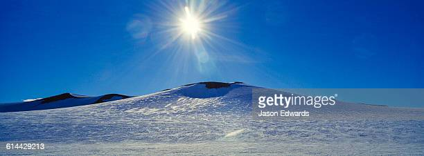 the sun rises above a snow-covered hill overlooking the ross ice shelf. - ross ice shelf stock photos and pictures