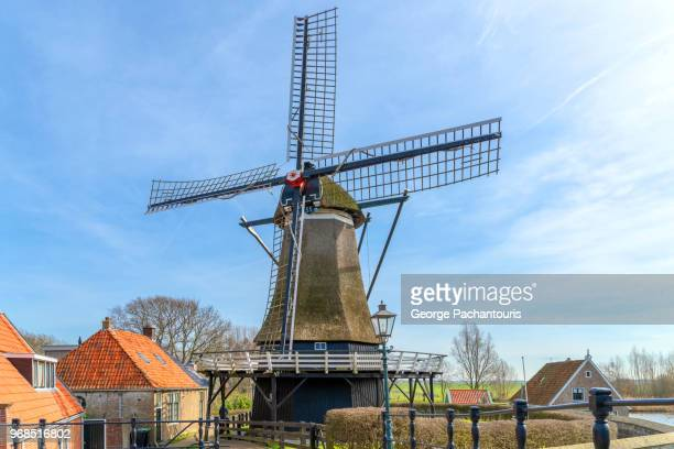 windmill against sky with few clouds - molen stockfoto's en -beelden