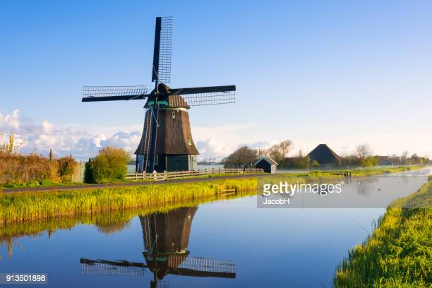 windmill along a canal - netherlands stock pictures, royalty-free photos & images