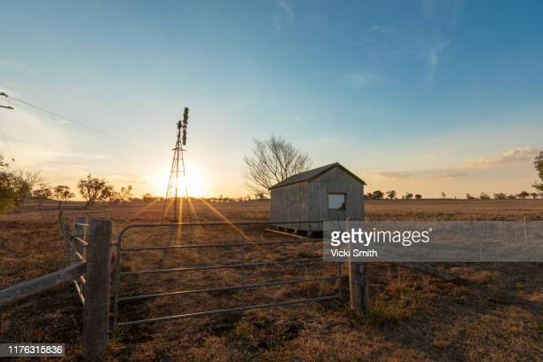 windmill and old shed out in the country at sunset - rustic stock pictures, royalty-free photos & images