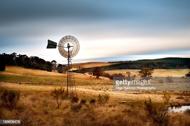 windmill and rolling hills, charming countryside - traditional windmill stock photos and pictures