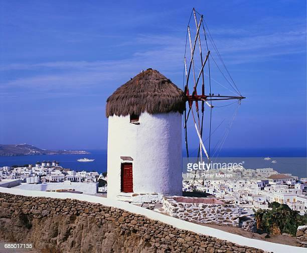 windmill and view of mykonos by the coast, cyclades, greece - lugar famoso local fotografías e imágenes de stock