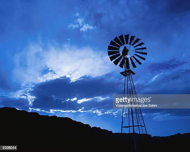 windmill at dusk with cloudy sky - american style windmill stock pictures, royalty-free photos & images