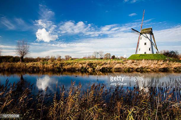 windmill by damse vaart canal - damme stock pictures, royalty-free photos & images