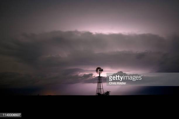 windmill illuminated at night by listening through storm clouds, darrouzett, texas, usa - country texas lightning stock pictures, royalty-free photos & images