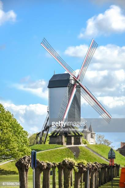 Windmill in Bruges with Kruispoort on background under dramatic sky, Flanders, Belgium