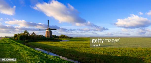 windmill in dutch polder - old windmill stock photos and pictures