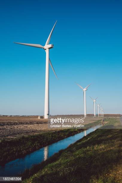 windmill on field against clear blue sky - bortes stock-fotos und bilder