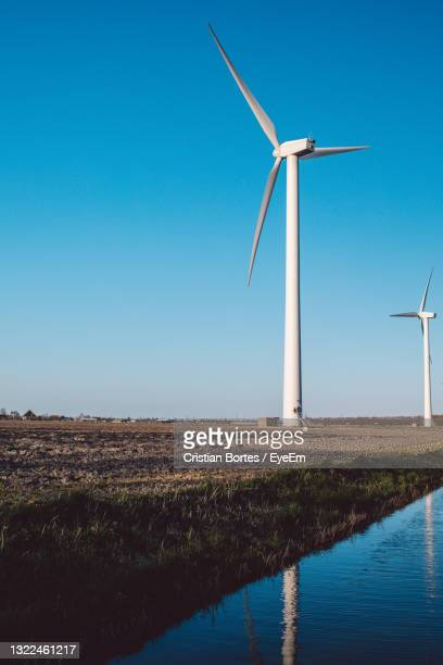 windmill on field against clear blue sky - bortes stock pictures, royalty-free photos & images